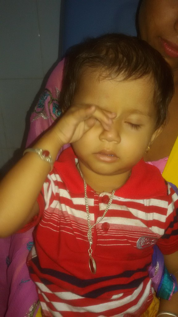 A young female infant rubbing her right eye with her knuckle.